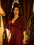 Micheline Pitt, standing in a gothic style room, models the Bauhaus top in oxblood by La Femme En Noir.