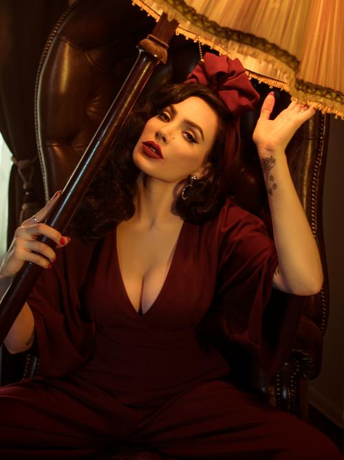 Micheline Pitt, tilting a lamp to her face, models the Bauhaus top in oxblood.