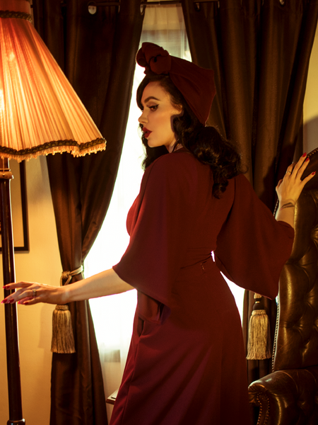 A back shot of Micheline Pit  standing in a gothic style room modeling the Bauhaus top in oxblood by La Femme En Noir.