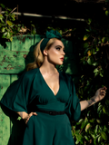 Micheline Pitt stands in a lush garden while modeling the Bauhaus top in hunter green from La Femme En Noir.