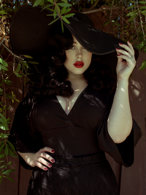Rachel stands under a tree with her hand on a black wide brim hat while modeling the Bauhaus top in black from La Femme En Noir.