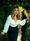Stepping through a wooden garden door surrounded by green leaves, Micheline Pitt models the New Bishop Blouse in Ivory paired iwth a form fitting pencil skirt.