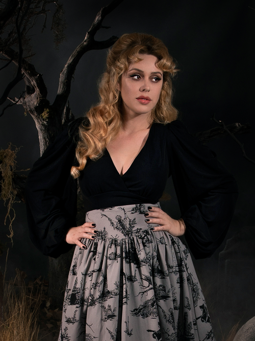 With her hands resting on her hips, Linda looks away while wearing the New Bishop Blouse in Black paired with a grey Sleepy Hollow inspired skirt.