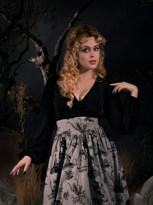 Linda standing amongst tombstones in a spooky graveyard models the New Bishop Blouse in Black from goth retro clothing maker La Femme en Noir.