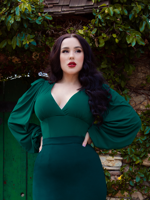 Rachel, with her hands on her hips, models the Bishop blouse in hunter green from La Femme En Noir.