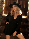 A Blonde Micheline Pitt modeling the Bishop Blouse in Black while standing in front of her garden gate.