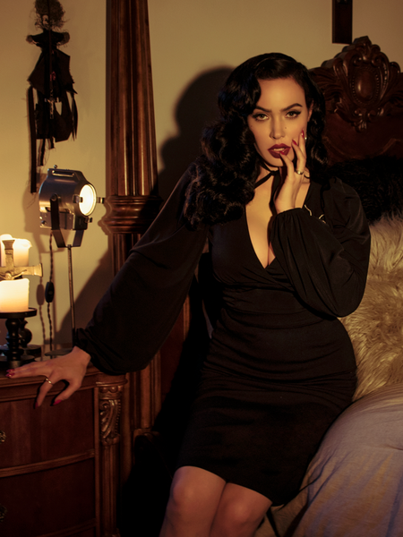 Micheline Pitt photographed on the side of her bed while wearing the Bishop Blouse in Black.