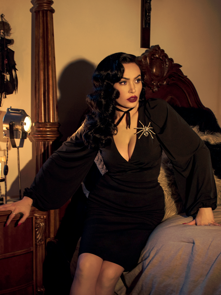Micheline Pitt sat on the side of her bed while wearing the Bishop Blouse in Black.
