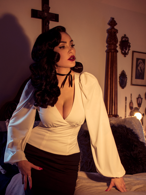 Micheline Pitt leans against a bed in a gothic bedroom while modeling the Bishop blouse in ivory by La Femme En Noir.
