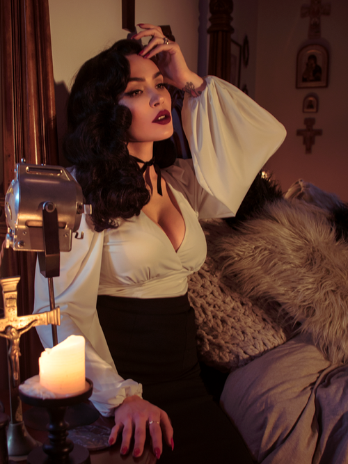 Micheline Pitt sits in a gothic bedroom while modeling the Bishop blouse in ivory by La Femme En Noir.