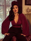 Micheline Pitt sits on a tufted leather couch while modeling the Bishop blouse in oxblood by La Femme En Noir.
