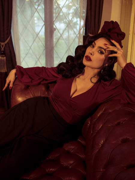 Micheline Pitt posing on a leather couch while wearing the New Bishop Blouse in Oxblood from La Femme en Noir.