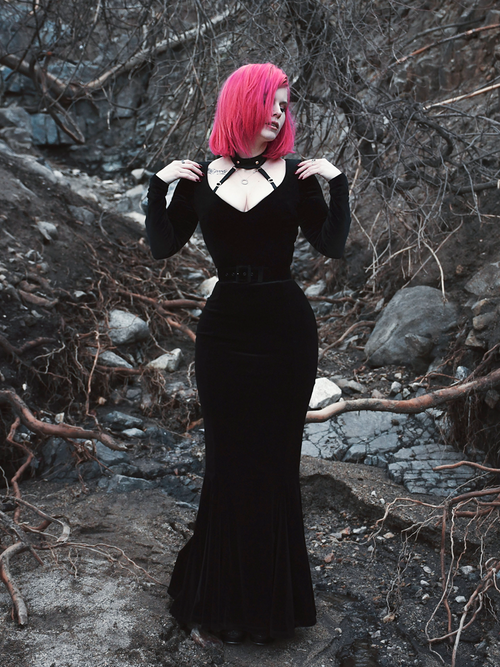 A full length shot of Mackenzie modeling the Black Marilyn gown in black paired with a harness.