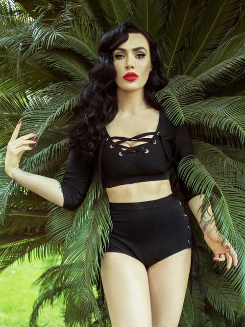 Micheline Pitt stands in front of palm tree fronds while looking at the camera modeling the Trinity swim top from La Femme En Noir.