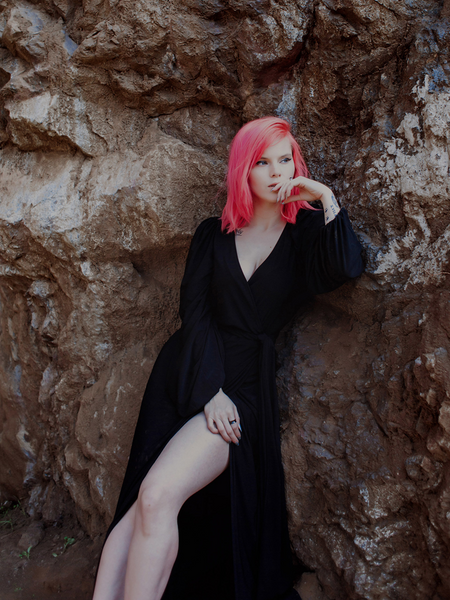 Model Mackenzie posing in front of a rock wall while wearing the Black Widow Wrap Gown in Solid Black from La Femme en Noir.