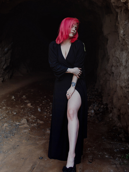 Full body length picture of model Mackenzie thrusting her leg out while wearing the Black Widow Wrap Gown in Solid Black from La Femme en Noir.