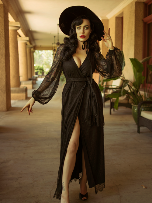 Micheline Pitt modeling the Black Widow Wrap Gown in Black Lace paired with a black sunhat.
