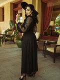 Micheline Pitt with her body facing away from the camera, subtly turns her head back while wearing the Black Widow Wrap Gown in Black Lace.