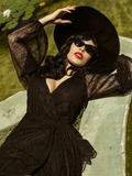 Micheline Pitt laying down and sunbathing while modeling the Black Widow Wrap Gown in Black Lace.