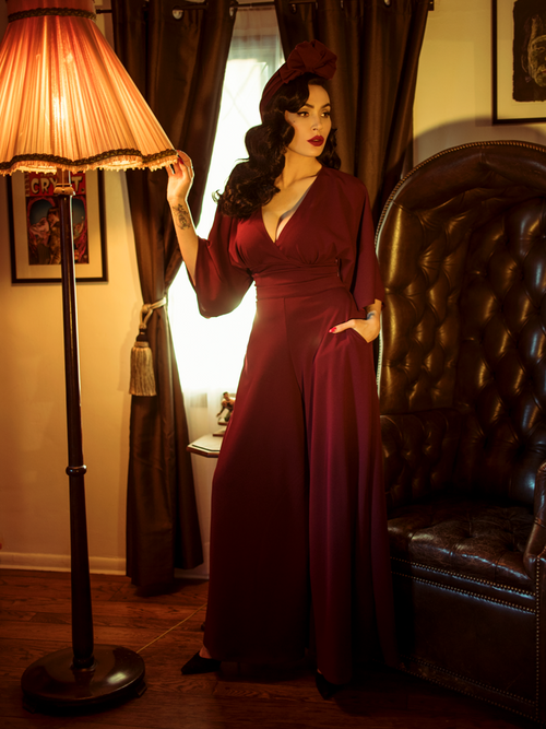Micheline Pitt standing next to a gothic style leather chair while modeling the Black Widow palazzo pants in oxblood by La Femme En Noir.