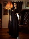 Rachel Sedory with her hand on her hip and another resting at her side models the Black Widow Palazzo Pants in Black from La Femme en Noir.