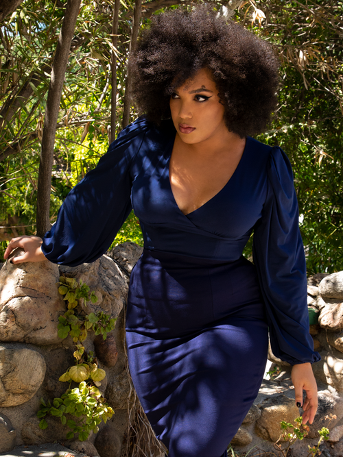 Ashleeta explores a lush garden while modeling the Bishop blouse in navy from La Femme En Noir.