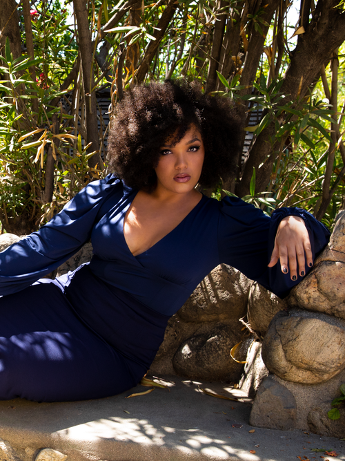 Ashleeta lounges on a rock bench while modeling the Bishop blouse in navy from La Femme En Noir.