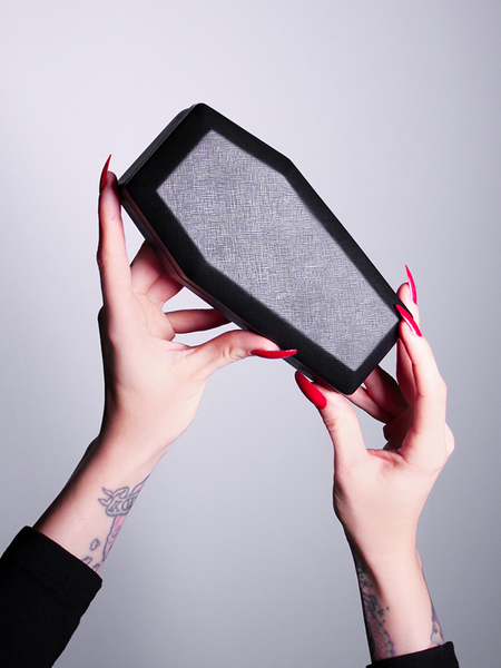 The Vamp Batwing Sunglasses in Black coffin case being held up by fair skinned hands.