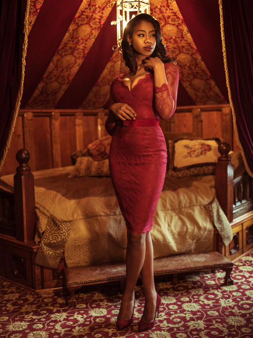 A full length photo of Chelsea standing in a moody boudoir modeling the La Dentelle dress in crimson.