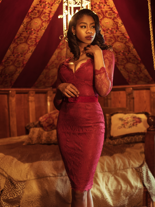 A stylized photo of Chelsea standing in a moody boudoir modeling the La Dentelle dress in crimson.