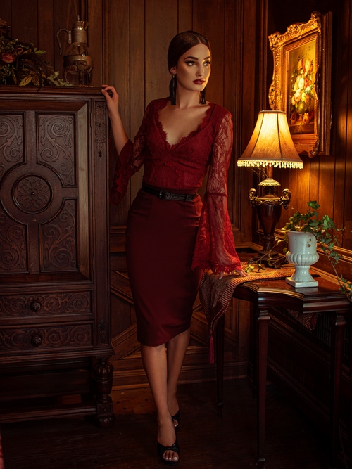 Aliza standing in a dimly lit room modeling the Vamp pencil skirt in oxblood.