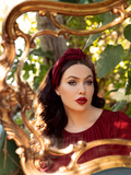 Micheline Pitt gazing into a gold-plated mirror  while wearing the goth vintage inspired Art Deco Head Scarf in Crimson Ponte paired with a similarly colored flowy top.