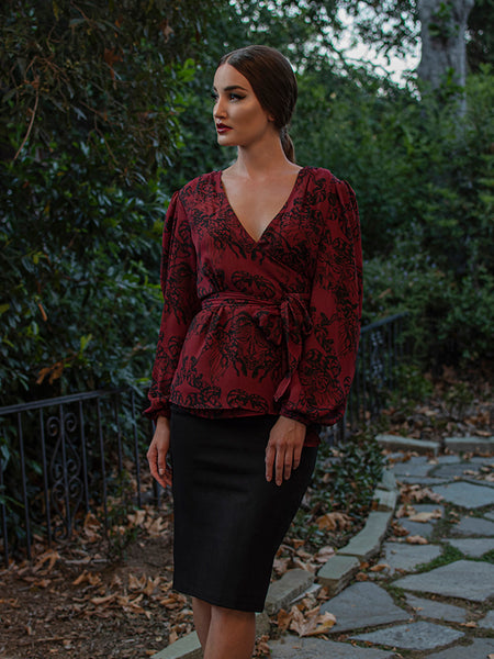 Aliza looking off camera models the Georgette wrap top in gorgon print paired with a black pencil skirt.