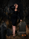 Full length image of Micheline Pitt leaning on a tombstone while wearing a black gothic style dress.