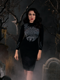 Micheline Pitt wearing the Sleepy Hollow Hessian Dress in Black while standing in a foggy graveyard.