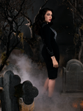 Profile shot of Micheline Pitt modeling the Sleepy Hollow Hessian Dress in Black from gothic dress maker La Femme en Noir.