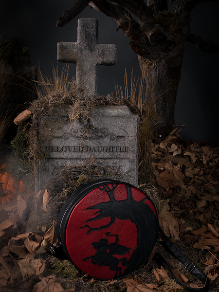 Gothic style bag placed against a tombstone.