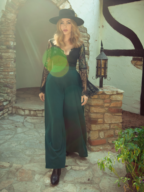 Micheline Pitt walks out of a Tudor style home modeling the Black Widow palazzo pants in hunter green.