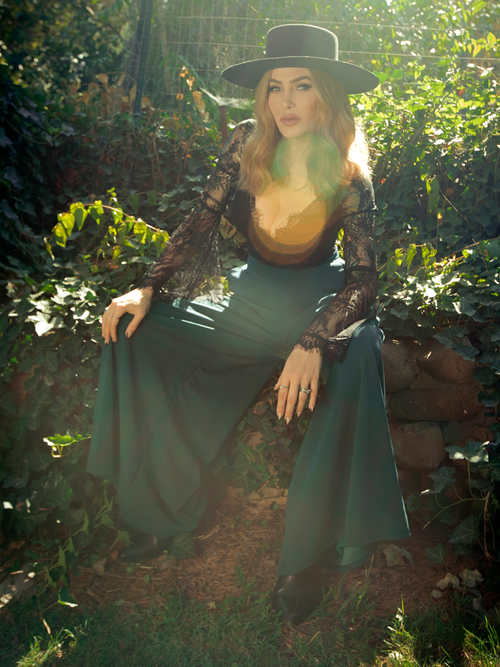 Micheline Pitt sits in a lush garden while modeling the Black Widow palazzo pants in hunter green.