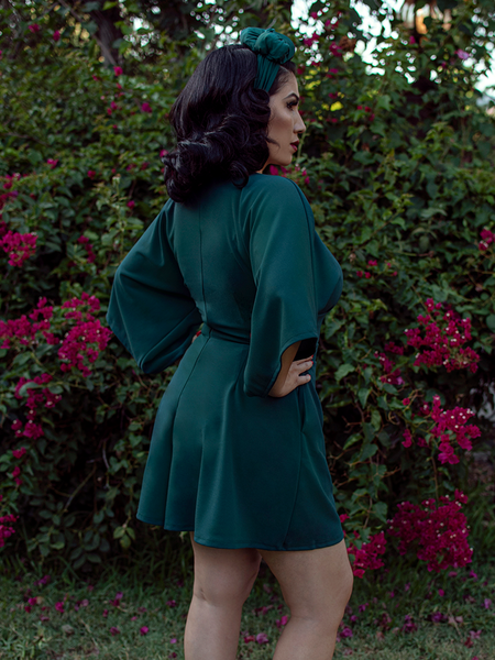 A back shot of Erika standing in a lush garden With her hands on her hips while modeling the Bauhaus top in hunter green from La Femme En Noir.