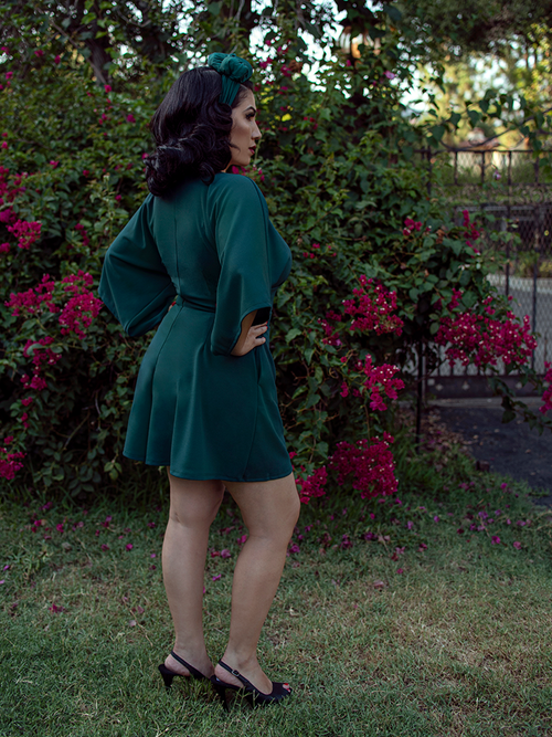 A back shot of Erika, with her hands on her hips in a garden, models the Black Widow tap shorts in hunter green from La Femme En Noir.