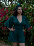 Erika stands in a lush garden With her hands on her hips while modeling the Bauhaus top in hunter green from La Femme En Noir.