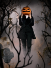 A mysterious figure holds the Sleepy Hollow Pumpkin Bag in front of their face while standing amongst fog covered tombstones.
