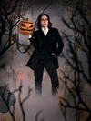 Micheline Pitt dressed as Ichabod Crane, holds the Sleepy Hollow Pumpkin Bag up on the palm of her hand.