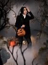 Reaching up to move the hair away from her brow, Micheline Pitt trudges through a fog covered graveyard scene while carrying the Sleepy Hollow Pumpkin Bag.