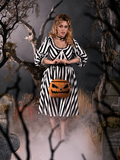 Linda holding a pumpkin bag while standing in a foggy cemetery while wearing a black and white striped gothic dress.