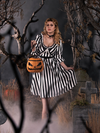 Linda, posing a black and white striped goth dress holding the Sleepy Hollow Pumpkin bag while standing in a foggy cemetery.
