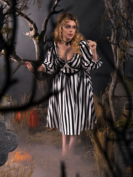Linda tip-toeing through a graveyard while wearing a black and white striped gothic dress.