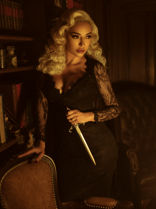 A stylized photo of Cindy, with a dagger in hand, modeling the La Dentelle dress in black.
