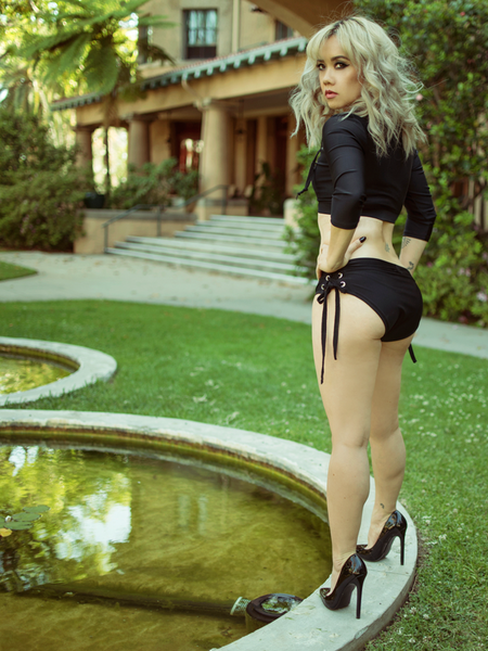 Lynh stands at the edge of a pond looking over her shoulder while modeling the Trinity side lace swim bikini bottoms.